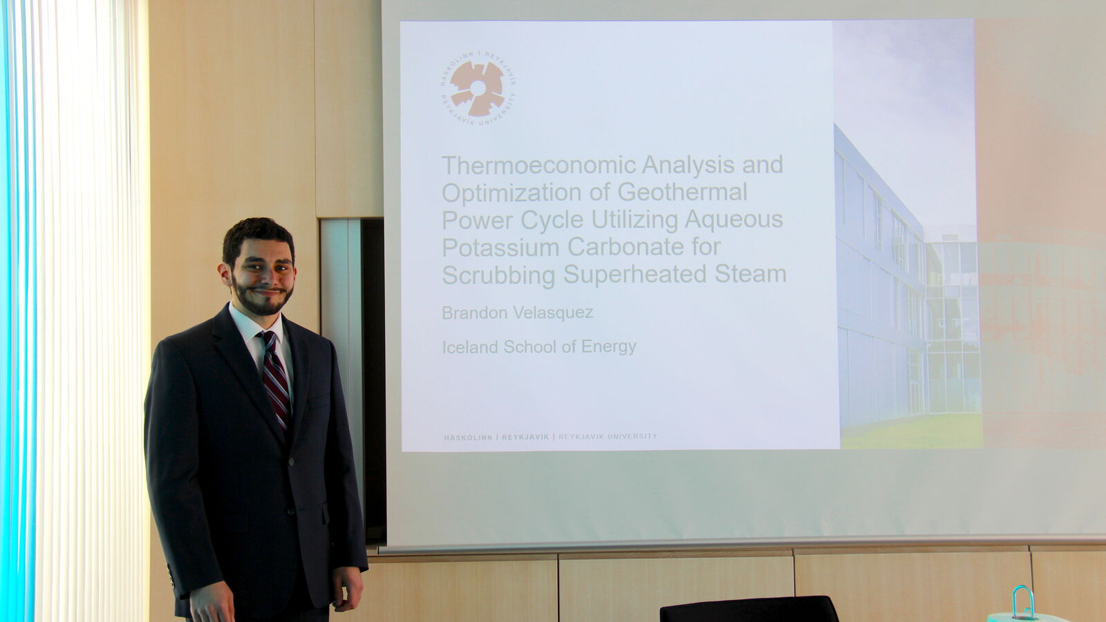 Brandon Velasquez smiling in front of his presentation title page before his thesis defence.