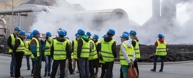A group of students in neon vests visit a geothermal powerplant